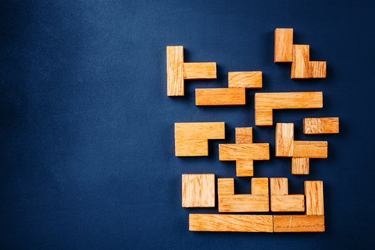 Different geometric shapes wooden blocks arrange in solid figure on a dark background. Creative, logical thinking and problem solving concept. Copy space
