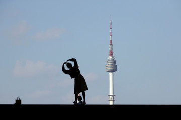 A woman posing for photographs is silhouetted against the backdrop of N Seoul Tower in Seoul