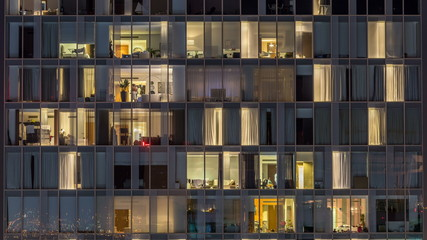 Windows of the multi-storey building of glass and steel lighting inside and moving people within timelapse Fototapete