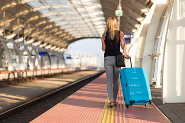 Woman with blue baggage suitcase walking on train station