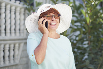 aged woman talking on phone. old lady in the Park. Sunny day, happy mood. happysenior woman with phone