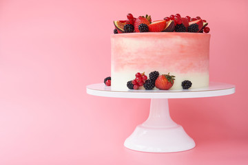 Cake with whipped pink cream, decorated with fresh strawberries, blackberry, figs and red currant on pink background. Picture for a menu or a confectionery catalog.
