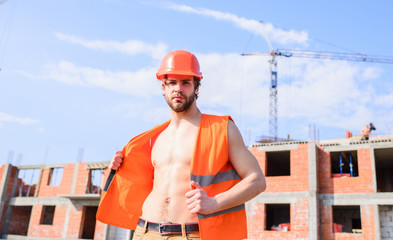 Builder orange vest helmet work construction site. Builder sexy muscular torso macho dream of every woman. Sexy macho foreman. Guy protective helmet stand in front of building made out of red bricks