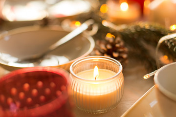 christmas, holidays and decoration concept - candle burning on table served for festive dinner at home