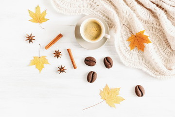 Autumn or winter cozy composition. Cup of coffee, warm knitted plaid, chocolate cookies, cinnamon sticks, aniseed star and dry leaves on a white background. Flat lay, top view, copy space