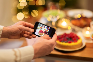 food, technology and holidays concept - close up of male hands photographing cake by smartphone at christmas dinner