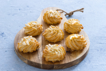 Almond pastry on chopping board on blue background