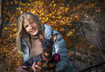 Woman walks in autumn park with little dog