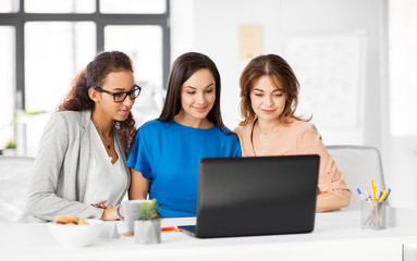 business, teamwork and people concept - female team or businesswomen with laptop computer working at office