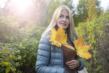 Pretty woman with autumn maple leaves