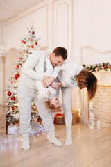 happy young family tossing up their little daughter smiling, stand against beautiful light interior with a Christmas tree and a white fireplace. Christmas family portrait. Baby look at camera