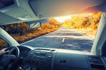 The car rides through a picturesque autumn highway.