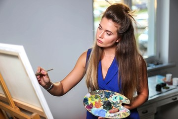 young beautiful woman painter paints painting by brush and oil paints in studio.