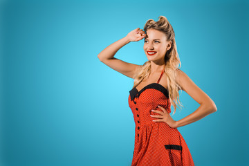 portrait of beautiful smiling pin up woman in retro style dress looking away on blue backdrop