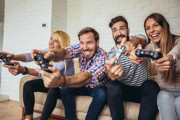 Group of friends play video games together.