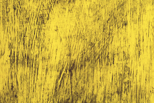 A wooden wall is covered with bright rich old paint. Old yellow wood background texture