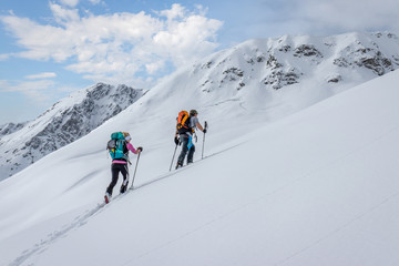 Ski touring couple hiking up a summit in the alps Wall mural