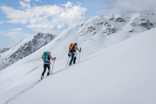 Ski touring couple hiking up a summit in the alps