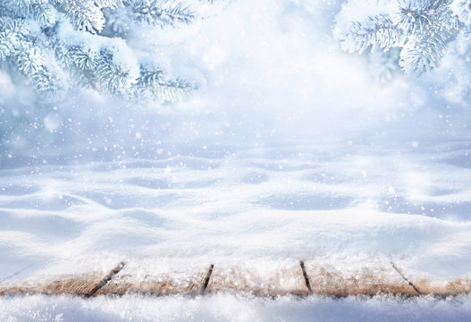 Winter christmas scenic background with copy space. Wooden flooring was strewn with snow in forest and branches of fir-trees covered with snow on the nature.