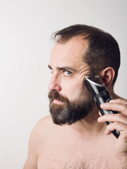Bearded man shaving his face