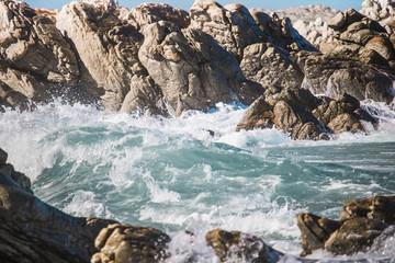 Crashing wave hitting rocks on the shore.