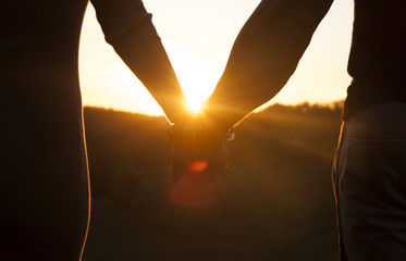 Romantic couple holding hands and watching a beautiful sunset