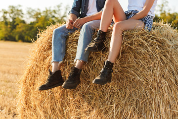 Cropped photo of lovely man and woman sitting on big haystack in golden field, during sunny day