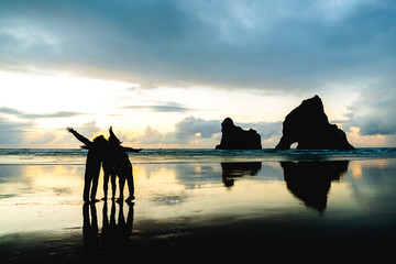 A group of people taking a photo with with famous rocks. Sunset scene golden light and silhouette. Wharariki Beach Nelson, South Island, New Zealand.