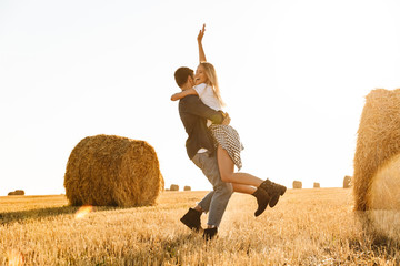 Photo of young couple man and woman having fun while walking through golden field with bunch of haystacks, during sunny day