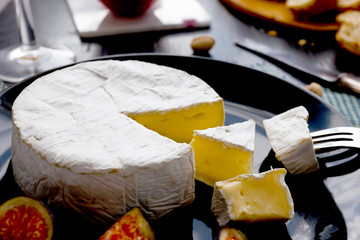 Camembert cheese on a black plate sliced with figs and fresh bread