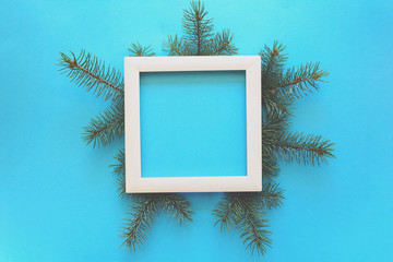 Christmas Border. Fir tree branches and white wooden frame on blue paper background. Top view. Copy space. Toned
