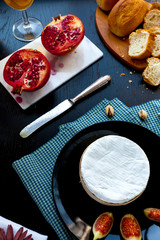 Camembert cheese on a black plate with figs, pistachios and wine in a glass, cut garnet on marble stone, fresh bread