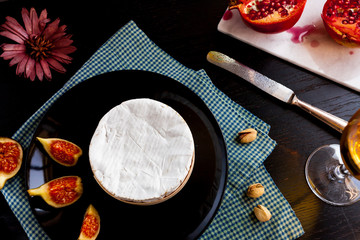 Camembert cheese on a black plate with figs, pistachios and wine in a glass, cut garnet on marble stone, top view