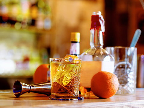 Old fashioned cocktail, orange, bottles and beaker on the bar counter
