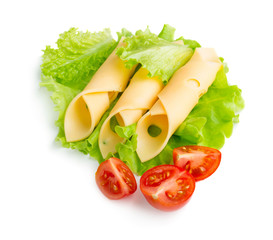 Cheese slices with salad leaves and tomatoes