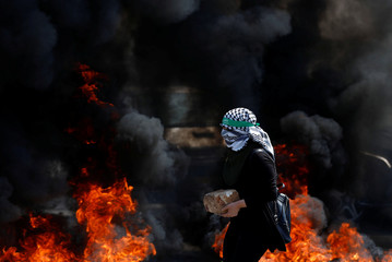 Palestinian girl carries a rock during clashes with Israeli troops at a protest near the Jewish settlement of Beit El, near Ramallah, in the occupied West Bank