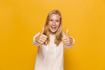 Photo of young female student or school girl with dental braces showing thumbs up, isolated over yellow background