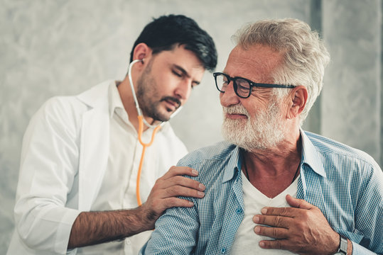 Medical Doctor is Examining Physical Health of Patient in Examination Room, Physician Doctor Using Stethoscope Diagnosis Disease for Elderly Man While Consulting Medic Treatment. Health Care/Medicine