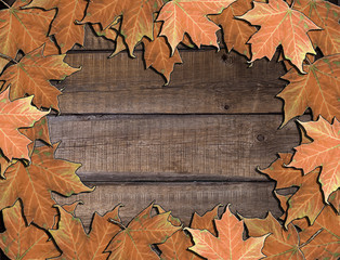 Fallen autumn maple leaves on a brown wooden background.