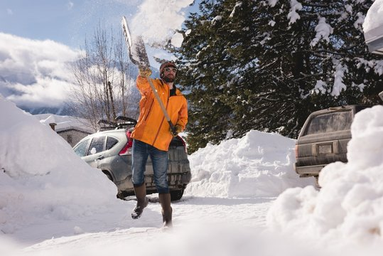 Man cleaning snow with snow shovel