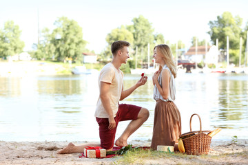 Young man making proposal to his girlfriend on romantic date near river