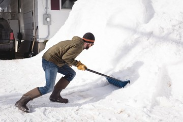 Man cleaning snow with snow pusher