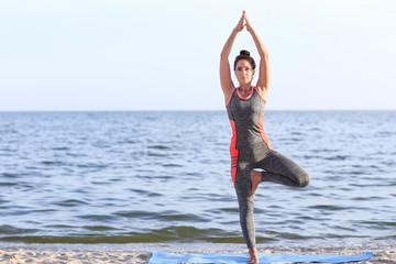 Woman practicing yoga on sea shore