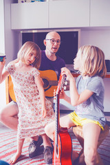 father teaching to his two daughter how to play guitar - teaching, learning, hobby concept