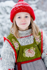 Little girl in knitted outfit in winter snow