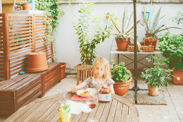 female child outdoor sitting table having breakfast - morning routine, eating, hunger concept