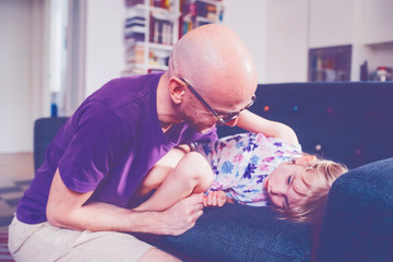 father with female child indoor on the couch cuddling - comforting, love, bonding concept