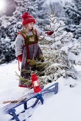 Little girl finding christmas tree in the forest in deep snow