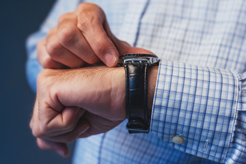 Businessman checking time on wristwatch