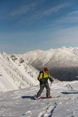 Male skier walking on a snowy mountain